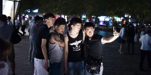 Des passants prennent des selfies, le 15 juillet 2015, devant le magasin de vêtements Uniqlo de Pékin où aurait été tournée la sextape
