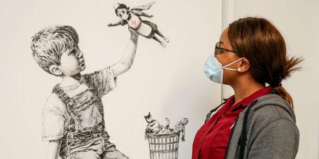 Un tableau du street artist britannique Banksy mettant les soignants à l'honneur s'est arraché aux enchères mardi à Londres à 16,75 millions de livres.