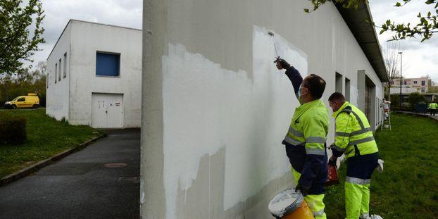 Des employés municipaux se sont employés à repeindre les murs pour recouvrir les inscriptions racistes.